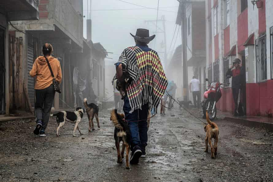 Displaced people walk in rain drenched street with dogs