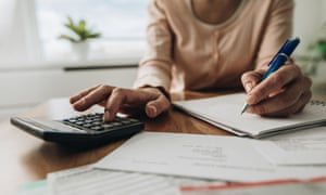 Close up of woman planning home budget and using calculator