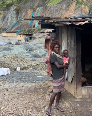 Families live in the disused mine pit at Panguna, attempting to make a living from alluvial mining. Polluted, unnaturally blue water, contaminates the pit and there are frequent landslides.