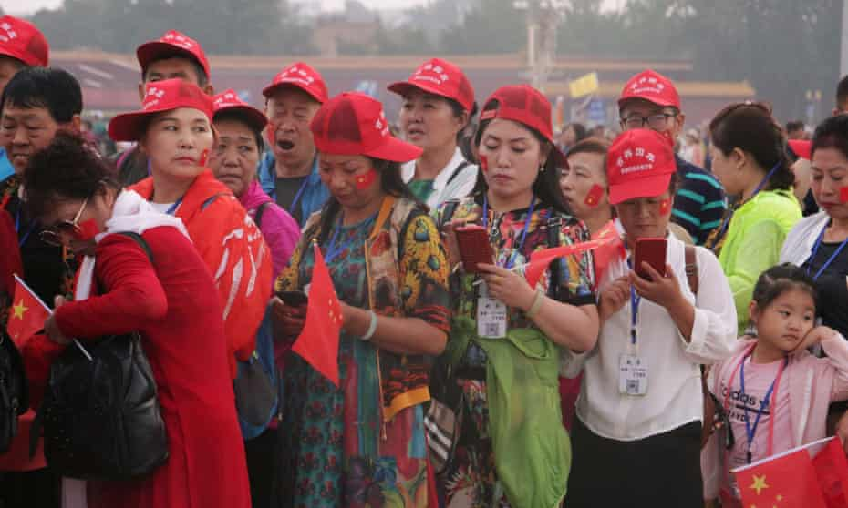 Tourists holding Chinese flags visit Tiananmen Square following the flag-raising ceremony held at sunrise, in Beijing on Tuesday.