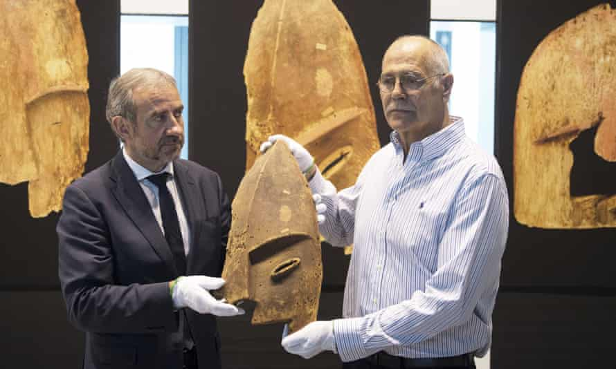 John Johnson, right, of the Chugach Alaska Corporation with Hermann Parzinger, the president of the Prussian cultural heritage foundation, show an item plundered from the graves of indigenous Alaskans.