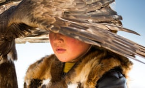 A child beneath the wing of his golden eagle in the Altai region in western Mongolia. The Kazakh nomads still use the birds for hunting.
