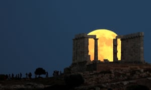 More yellow than red, the moon rise behind the Temple of Poseidon in Cape Sounion, Greece.