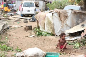 A young child sits among the debris.