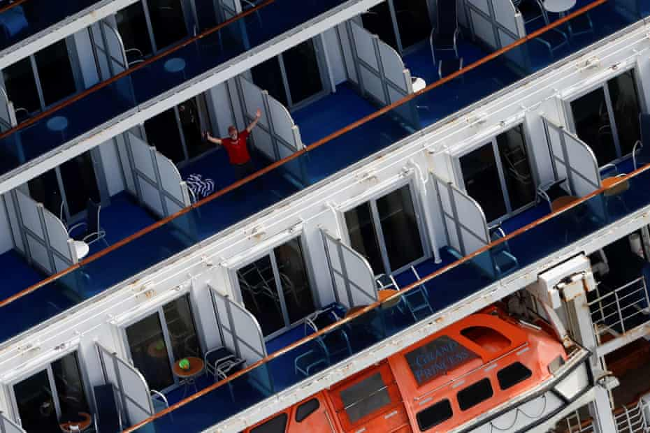 A passenger reacts from his cabin balcony as the Grand Princess docks at the port of Oakland on 9 March 2020.