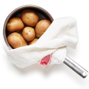 Bring the unpeeled potatoes to a boil, cook, then drain and cover with a tea towel, so they steam. Photos by Dan Matthews.