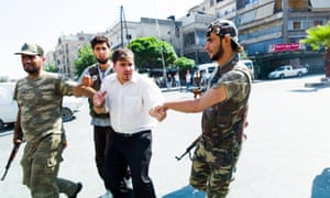 Free Syrian Army rebels holding a man suspected of belonging to government security forces in Aleppo in August 2012