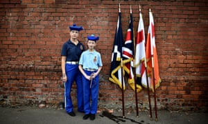 Flags rest on the wall behind a woman and a young girl dressed for the annual 12 July Orange march in Belfast