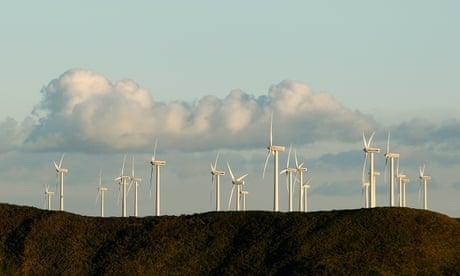 Turbinas de viento en una colina contra ráfagas de nubes en un cielo azul