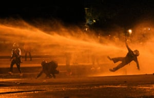 Bogotá, Colombia A demonstrator falls after being hit by water cannon during clashes with riot police during protests against the government of the Colombian president, Iván Duque