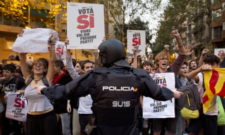 A Spanish national police officer tries to stop protesters calling for a referendum in Barcelona, Spain, amid a crackdown that has included the arrests of more than a dozen officials.