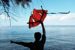 A man uses a life vest to guide a raft carrying Syrian and Iraqi refugees onto the island of Lesbos from Turkey.