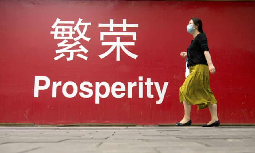 A woman in China passes a red sign marked 'prosperity'