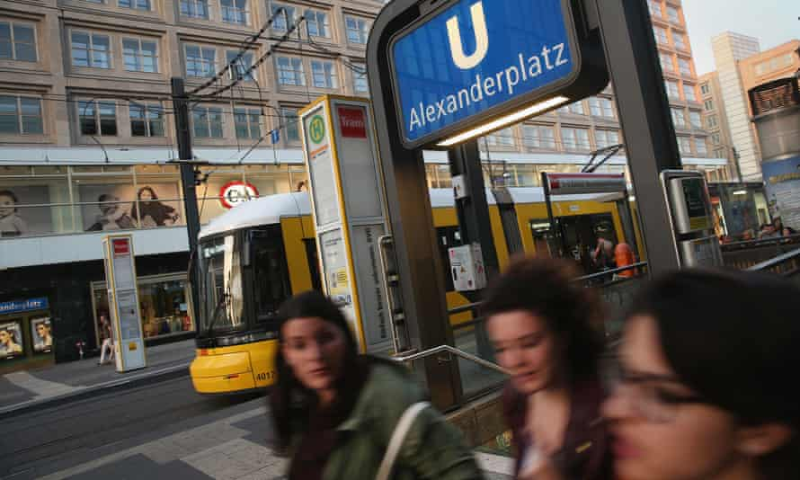 Young women walk past the entrance to Alexanderplatz U-Bahn station in Berlin, Germany.
