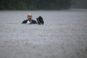 A man wades out through floodwaters Thursday in Patton Village, Texas.