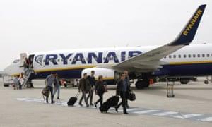 Passengers disembark from a Ryanair plane