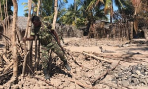 A soldier clears wreckage after a 2018 attack in Naunde, Mozambiqu