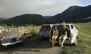 Steve and Nancy Morse talk on their phones as they watch a wildfire burn above their home on Twisp River Road
