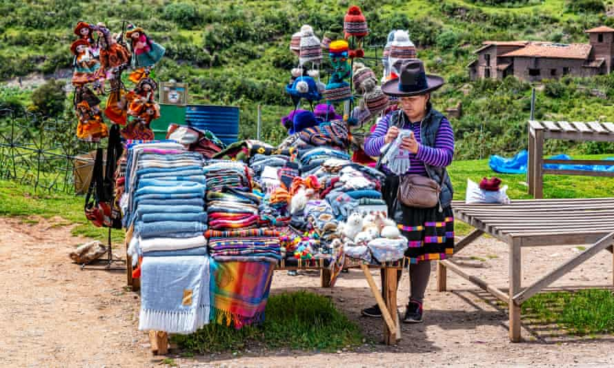 A woman sells traditional Peruvian clothes and textiles in Chinchero