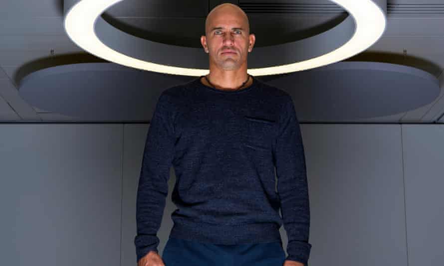Kelly Slater in a simple crew-neck jumper, with a circular ceiling light framing his head