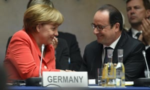 French President Francois Hollande (R) and German Chancellor Angela Merkel smile at each other as they attend the Petersberg Climate Dialogue conference in Berlin today.
