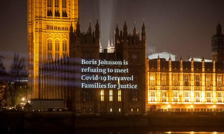 """A video with the message """"Boris Johnson is refusing to meet Covid-19 Bereaved Families for Jusice"""" projected on to the Houses of Parliament."""