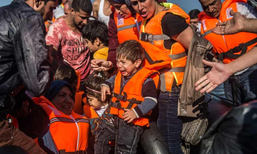 Syrians migrant cry as they reach land in an overloaded rubber dinghy on the coast near Skala Sikaminias, Lesbos island, Greece on Sunday.