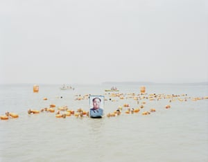 People crossing the Yellow River with a photo of Mao Zedong, Henan, 2012