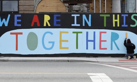 Erin Guido finishes painting the slogan 'We are in this together!' at a construction site during the coronavirus pandemic.