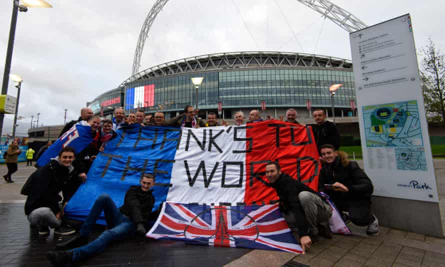 French fans pose with a french flag with the words 'Thanks To The World' as they arrive at Wembley Stadium ahead of the football match between England and France on November 17