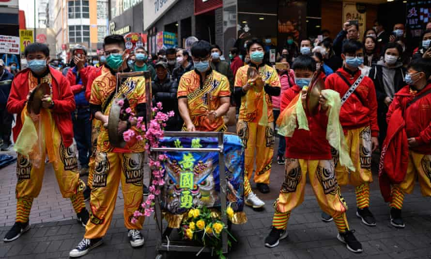 A Chinese lion dance team wear face masks during a performance in the Mong Kok district of Hong Kong. Health workers are set to go on strike over the government's refusal to close the China border to contain the coronavirus outbreak.