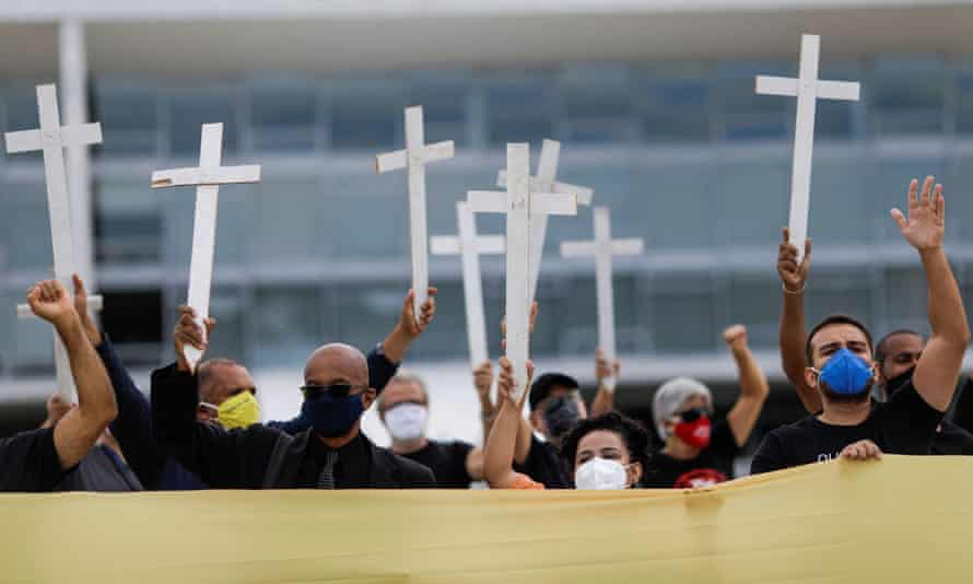 Demonstrators hold crosses as they take part in a protest against Brazil's President Jair Bolsonaro and his handling of the coronavirus disease (COVID-19) outbreak, in Brasilia, Brazil on 19 March 2021.