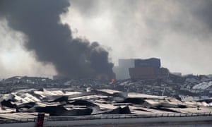 Smoke rises amid mangled wreckage at the site of a series of explosions in Tianjin.