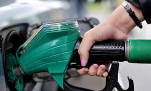 A motorist fillers her car at a petrol pump