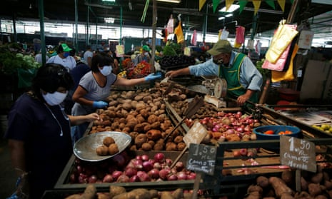 A woman buys produce at Lima's central market as Peru extended a nationwide lockdown amid the outbreak of the coronavirus disease.