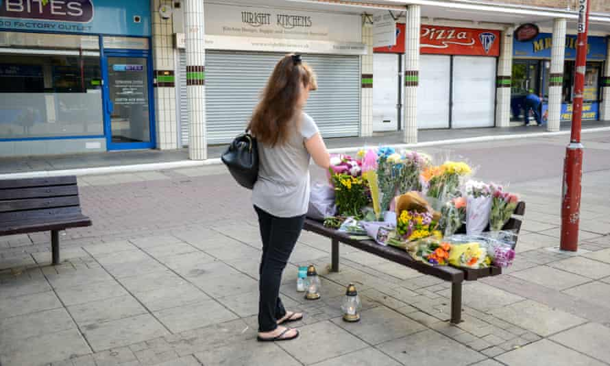 A woman adds flowers to a tribute to Arkadiusz Jóźwik, a 40-year-old Polish man murdered in Harlow on 27 August.