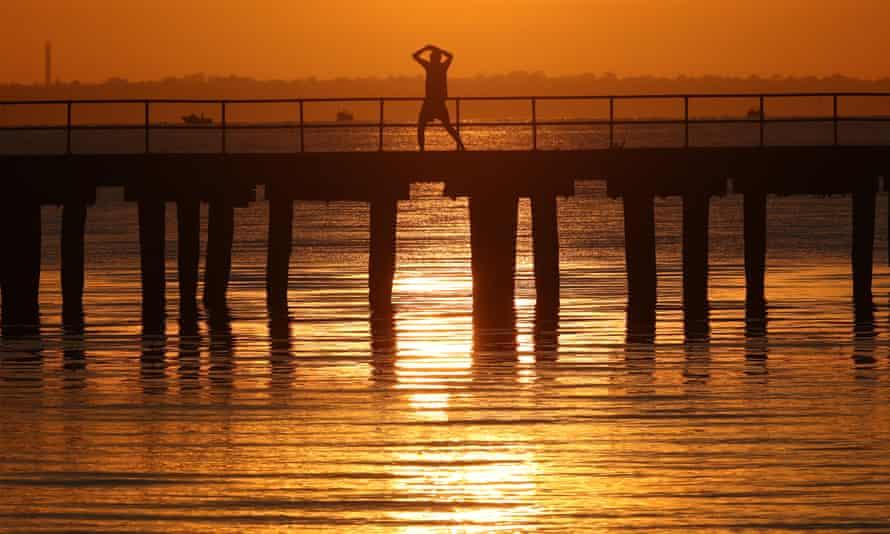 A men stretches during sunrise over Altona pier in Melbourne.