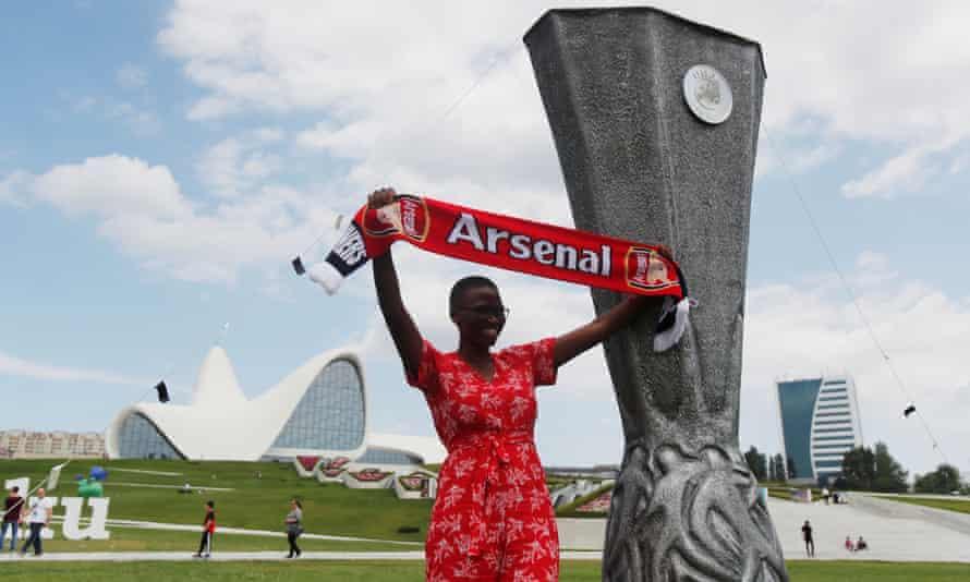 An Arsenal fan poses next to a giant replica of the Europa League trophy in Baku.
