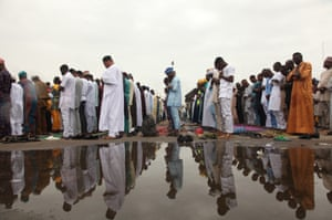 Worshippers reflected in water