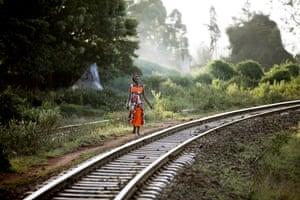 A woman walks along rail tracks in Kenya