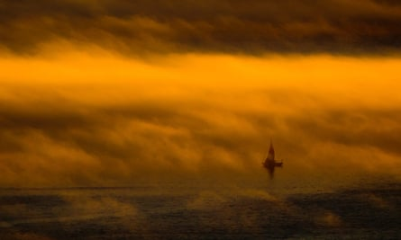 A sailboat as dense fog hangs over the water at sunset.