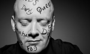 Matthew Todd, eyes closed, with words like 'dirty', 'queer', 'fag' and 'Aids' written in pen on his face and shaved head