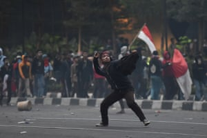 A protester throws a stone during clashes with police in Jakarta.