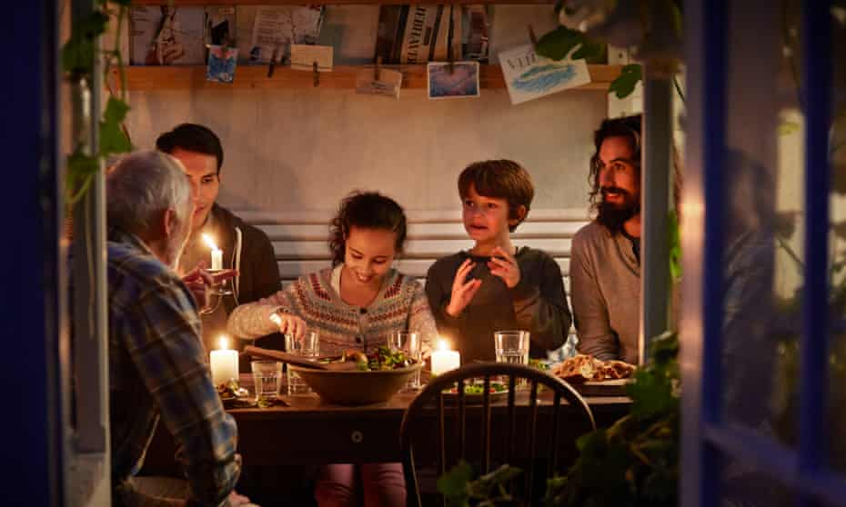 A family relaxing together around a candlelit table epitomises hygge.