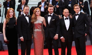 A cast photo – four men in tuxedos and two women in evening gowns stand in a line on the red carpet