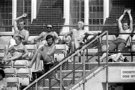 Spectators soak up the sun while watching Surrey play Lancashire at The Oval.