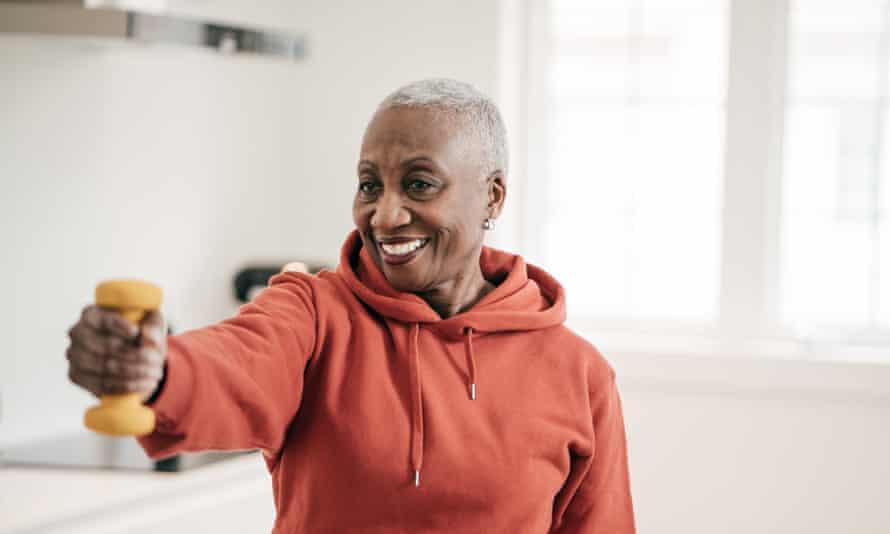 زنی که در خانه با دمبل ورزش می کند