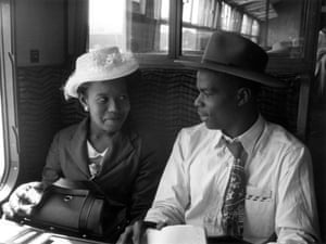 A newly arrived couple travel by train to London