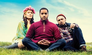 Yasmine Akram (Tara), Samuel Anderson (Luke) and Adam Deacon (Tony) sitting on grass with the sky behind in THE RETREAT