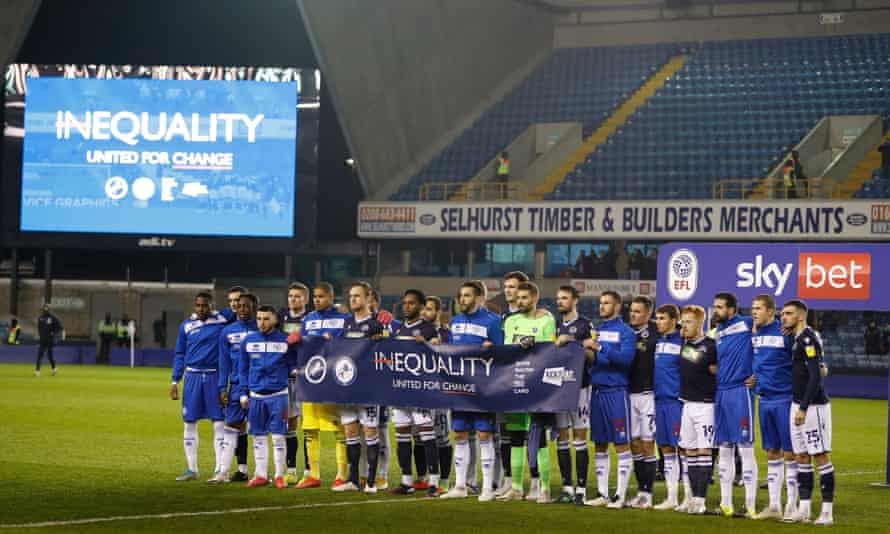 Millwall and QPR players holding up an equality banner before their match